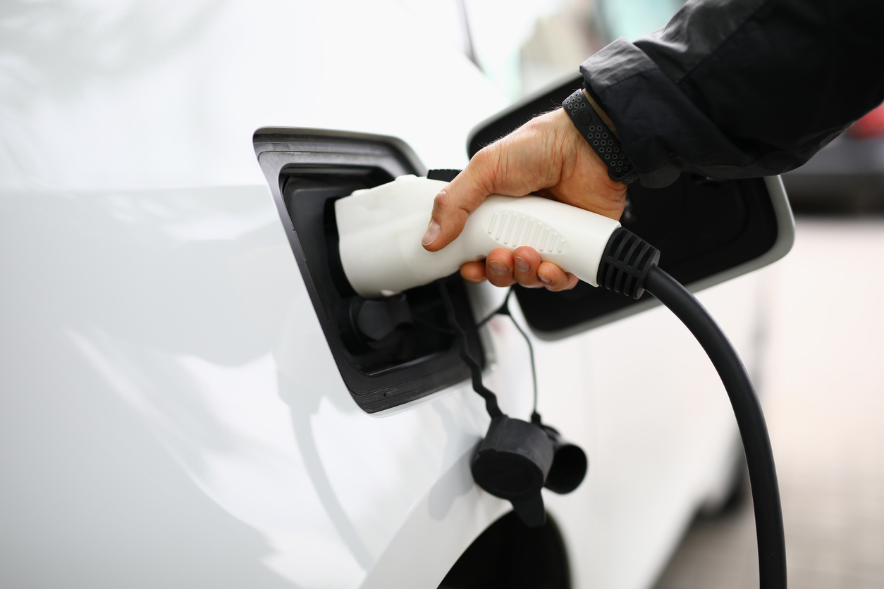 White electric car be recharged at charging station.